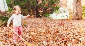 Fille heureuse d'enfant en bas âge ratissant des feuilles Photo libre de droits