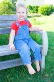 Fille heureuse d'enfant en bas âge s'asseyant sur un banc. Photos libres de droits