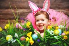 Fille heureuse d'enfant en lapin de Pâques de costume sur l'herbe et la Floride Photo libre de droits
