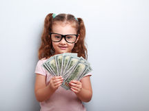 Fille heureuse d'enfant en verres tenant l'argent dans la main et le regard Image stock