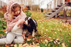 Fille heureuse d'enfant jouant avec son chien cavalier d'épagneul de roi Charles en automne images stock