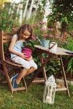 fille heureuse d'enfant jouant dans le jardin d'été, tenant la fleur de géranium dans le pot Images libres de droits