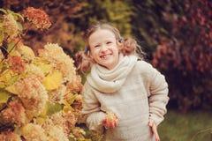 Fille heureuse d'enfant jouant dans le jardin d'automne près du buisson d'hortensia avec les fleurs sèches Photo libre de droits