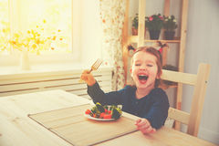 Fille heureuse d'enfant mangeant des légumes et des rires photo stock