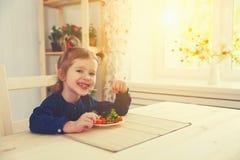 Fille heureuse d'enfant mangeant des légumes et des rires photographie stock