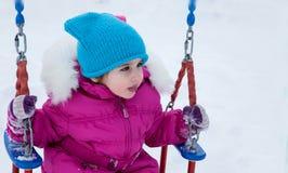 Fille heureuse d'enfant sur l'oscillation en hiver de coucher du soleil Peu d'enfant jouant sur une promenade d'hiver en nature Images libres de droits