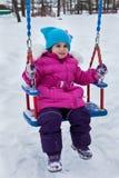 Fille heureuse d'enfant sur l'oscillation en hiver de coucher du soleil Peu d'enfant jouant sur une promenade d'hiver en nature Images stock