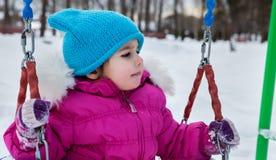Fille heureuse d'enfant sur l'oscillation en hiver de coucher du soleil Peu d'enfant jouant sur une promenade d'hiver en nature Photos stock