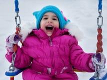 Fille heureuse d'enfant sur l'oscillation en hiver de coucher du soleil Peu d'enfant jouant sur une promenade d'hiver en nature Photo stock