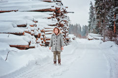 Fille heureuse d'enfant sur la route dans la forêt neigeuse d'hiver avec l'abattage d'arbres sur le fond Photographie stock libre de droits