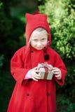 Fille heureuse d'hiver dans le manteau rouge se reposant près de l'arbre de Noël Cadre actuel Images stock