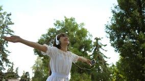 Fille heureuse dans des écouteurs sourire, tenant le smartphone à disposition, dansant en parc d'été Mouvement lent Belle fille banque de vidéos