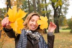 Fille heureuse dans des feuilles colorées de forêt d'automne Photo libre de droits