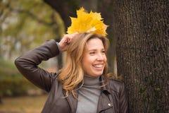 Fille heureuse dans des feuilles colorées de forêt d'automne Photos stock