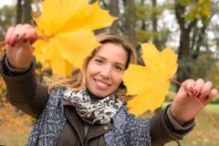 Fille heureuse dans des feuilles colorées de forêt d'automne Photo stock