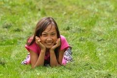 Fille heureuse dans l'herbe verte Photos libres de droits