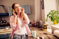 Fille heureuse dans la musique de écoute de sourire d'écouteurs à la maison Photos stock
