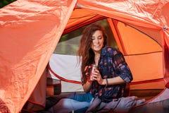 Fille heureuse dans la tente avec la bouteille de thermos image stock