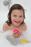 Fille heureuse dans le bain de bulle Photo stock