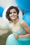 Fille heureuse dans le bal d'étudiants avec des ballons à air d'hélium Portrait d'une belle diplômée de fille dans une robe bleue Images stock