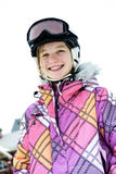 Fille heureuse dans le casque de ski à la ressource de l'hiver photographie stock libre de droits