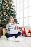 Fille heureuse dans le chapeau de Santa causant en ligne sur l'ordinateur portable Photographie stock