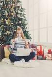 Fille heureuse dans le chapeau de Santa causant en ligne sur l'ordinateur portable Photo stock