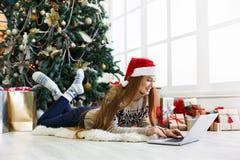 Fille heureuse dans le chapeau de Santa causant en ligne sur l'ordinateur portable Photos libres de droits