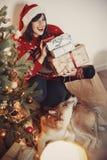 Fille heureuse dans le chapeau de Santa tenant des boîte-cadeau et la séance mignonne de chien photo libre de droits