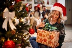 Fille heureuse dans le chapeau du ` s de Santa avec des cadeaux de Noël à la maison Photographie stock libre de droits