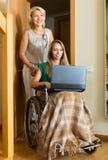 Fille heureuse dans le fauteuil roulant travaillant sur l'ordinateur portable Images libres de droits