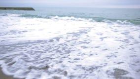Fille heureuse dans le manteau rose près de la mer pendant une tempête La mer lave ses empreintes de pas dans le sable clips vidéos