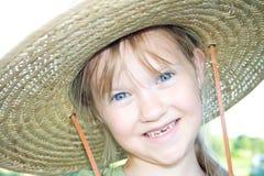 Fille heureuse dans un chapeau de paille avec l'expression drôle. Image stock