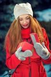 Fille heureuse dans un manteau et une écharpe rouges avec le cadeau dans une boîte rouge Photographie stock libre de droits