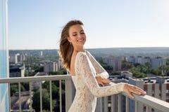 Fille heureuse dans une robe blanche sur une terrasse avec des vues de ville Image libre de droits