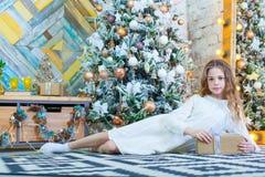 Fille heureuse de bel enfant avec le cadeau de Noël à la maison sur le plancher Photographie stock