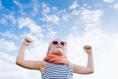 Fille heureuse de bel enfant dans des lunettes de soleil avec les mains ouvertes contre Images libres de droits
