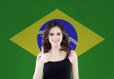 Fille heureuse de brune avec le pouce vers le haut de la pose sur le fond de drapeau du Brésil photos libres de droits