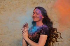 Fille heureuse de brune avec de longs cheveux bouclés jouant avec éclater la poudre sèche orange et bleue de Holi photo libre de droits