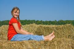 Fille heureuse de ferme s'asseyant sur une balle de paille. Photographie stock libre de droits