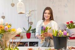 Fille heureuse de fleuriste appréciant le travail avec des fleurs Images libres de droits