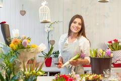 Fille heureuse de fleuriste appréciant le travail avec des fleurs Photographie stock