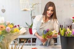 Fille heureuse de fleuriste appréciant le travail avec des fleurs Photo libre de droits