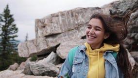 Fille heureuse de hippie de voyageur avec les cheveux venteux et position de sourire sur la montagne ensoleillée cheveux élégants banque de vidéos