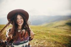 Fille heureuse de hippie de voyageur avec les cheveux venteux souriant, o debout image stock