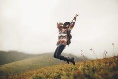 Fille heureuse de hippie de voyageur dans le chapeau, sautant avec le sac à dos et le SM image stock