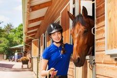 Fille heureuse de jockey avec le cheval de baie par des écuries d'équitation Photo stock