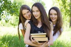 Fille heureuse de l'étudiant trois avec des livres en stationnement Photographie stock libre de droits