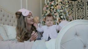 Fille heureuse de mère et d'enfant le matin de Noël sur le fond de l'arbre de Noël avec des cadeaux clips vidéos