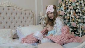 Fille heureuse de mère et d'enfant le matin de Noël sur le fond de l'arbre de Noël avec des cadeaux banque de vidéos